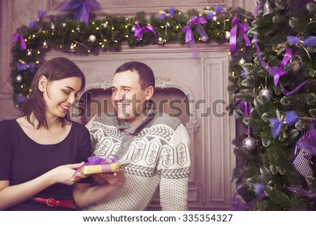 Beautiful happy young couple with present near christmas tree
