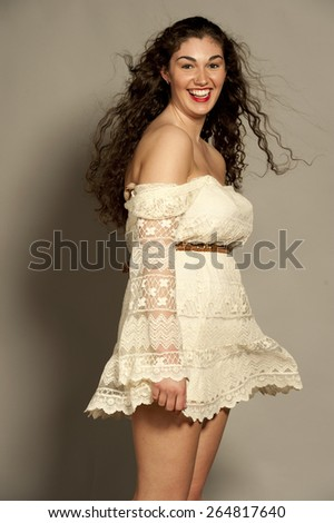 Beautiful happy young female brunette with curly hair in a studio setting while wearing a white dress on a gray background. - stock photo
