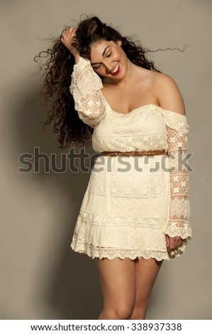 Beautiful happy young female brunette with curly hair in a studio setting while wearing a white dress on a gray background.