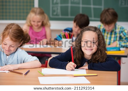Beautiful happy young girl in class at school looking up from her desk and notes to smile at the camera