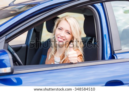 Beautiful happy young girl sitting in her car