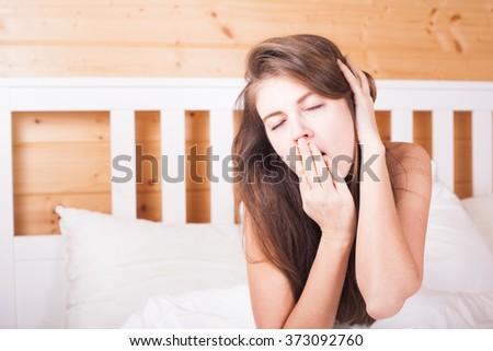 beautiful happy young long haired woman waking up in the morning and yawning in bed at home - stock photo
