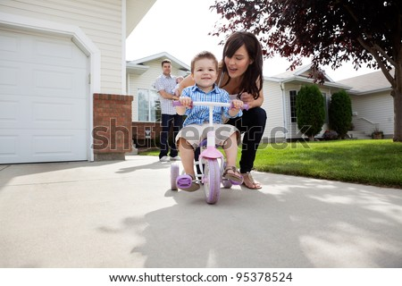 Beautiful happy young mother teaching her son to ride bike