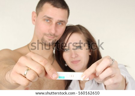 Beautiful, happy & young pregnant couple with pregnancy test - stock photo