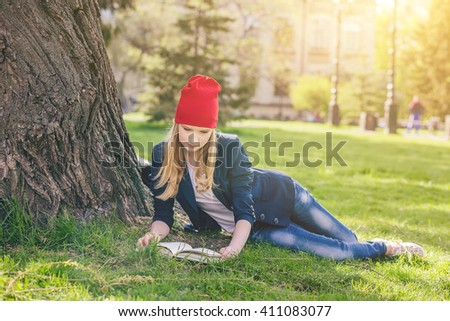 Beautiful, happy young student girl in red hat holding book lie down on green grass under the tree near the campus, university, school, education, pensive. Summer, spring green park, bright sunshine