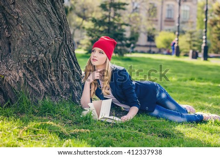 Beautiful, happy young student girl in red hat holding book lying near bag on green grass under the tree near the campus, university, school, education. Summer, spring green park, bright sunshine