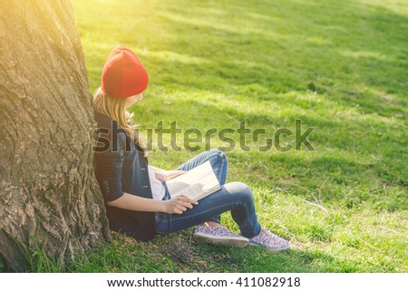 Beautiful, happy young student girl in red hat holding book sitting on green grass under the tree near the campus, university, school, education. Summer, spring green park, bright sunshine - stock photo