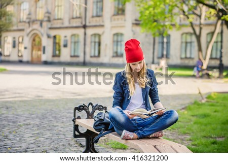 Beautiful, happy young student girl in red hat holding book sitting on the bench near the campus, university, school, education. Summer, spring green park - stock photo