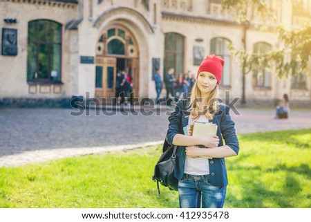 Beautiful, happy young student girl in red hat holding book standing on green grass under the tree near the campus, university, school, education. Summer, spring green park - stock photo
