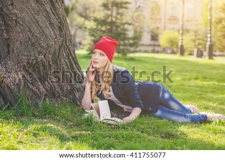 Beautiful, happy young student girl in red hat lying with books and backpack on green grass under the tree near the campus, university, school, education. Summer, spring green park, bright sunshine