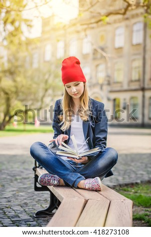 Beautiful, happy young student girl sitting on the bench on green grass near the campus, university, school, education in red hat holding book, spring green park, bright sunshine - stock photo