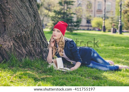 Beautiful, happy young student girl stands with books and backpack on green grass under the tree near the campus, university, school, education. Summer, spring green park