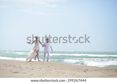 Beautiful happy young wedding couple of man and woman in white running along ocean beach shore on windy weather sunny day outdoor on blue sky background, horizontal picture