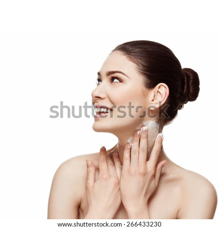 Beautiful happy young woman applying moisturizing cream on her neck. Beauty image. Copy space. Square composition. Isolated over white background. - stock photo