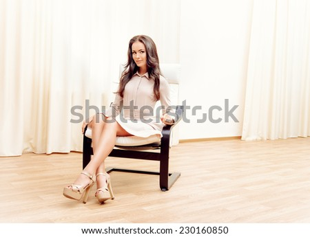 Beautiful happy young woman at home in a comfortable chair.
