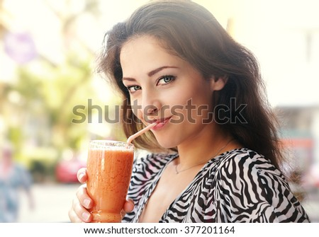 Beautiful happy young woman drinking healthy smoothie juice outdoor background. Closeup portrait - stock photo