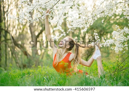 Beautiful happy young woman enjoying beauty in a flowering spring garden