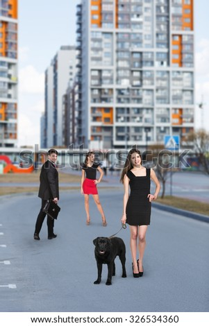 Beautiful happy young  woman in black dress with cute dog have fun on street - stock photo