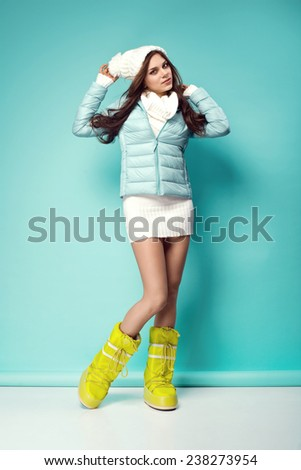 beautiful happy young woman in white warm long sweater, down jacket, winter cap and yellow snow shoes. Fashionable clothes - stock photo