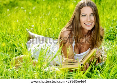 Beautiful happy young woman lying on a grass in the summer park and smiling. Holidays, vacation. - stock photo