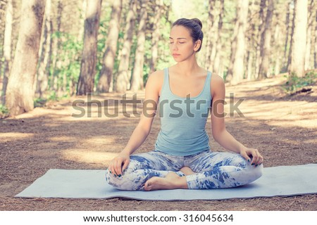 Beautiful happy young woman meditating doing yoga outdoors in summer autumn park - stock photo