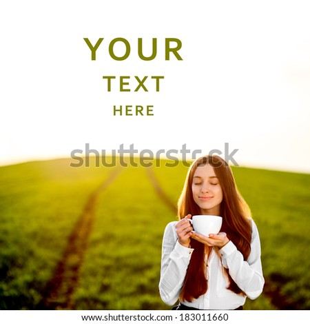 Beautiful happy young woman or girl smiling and enjoying coffee in the green field with space for text - stock photo