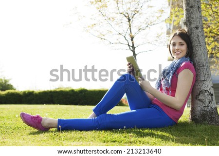 Beautiful happy young woman sitting on grass, enjoy sunny day and listening music with headphones while reading book. Happy young woman sitting on grass and reading a book.  - stock photo