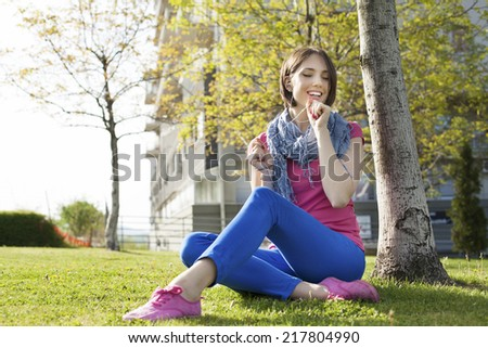 Beautiful happy young woman sitting on grass, enjoy sunny day and listening music with headphones while reading book, singing. - stock photo