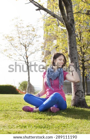 Beautiful happy young woman sitting on grass, enjoy sunny day and listening music with headphones while using a digital tablet. - stock photo