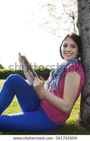 Beautiful happy young woman sitting on grass, enjoy sunny day and listening music with headphones while using digital tablet.