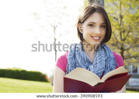 Beautiful happy young woman sitting on grass, enjoy sunny day and listening music with headphones and reading a book.