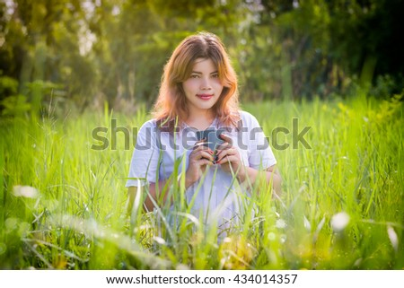 Beautiful happy young woman smiling and enjoying coffee in the green field under morning sunlight.