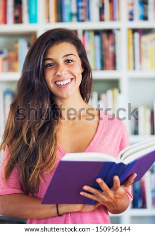 beautiful happy young woman standing with book in front of bookcase in a living room at home
