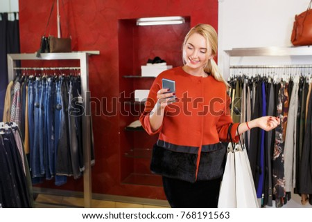 Beautiful happy young woman standing with white shopping bags and mobile phone in the store. Shopping concept