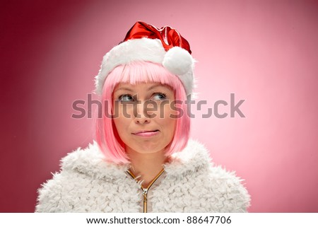 Beautiful happy young woman wearing pink wig and dressed as santa over red background. - stock photo