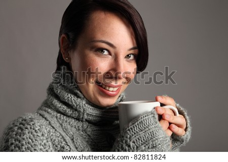 Beautiful happy young woman wearing thick wool sweater holding a mug of hot coffee. Shot against a grey background. - stock photo