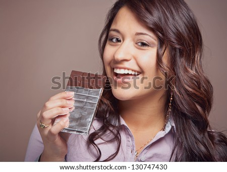 Beautiful happy young woman with chocolate bar - stock photo