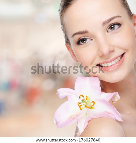 Beautiful happy young woman with lily on body at face - stock photo