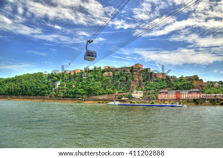 Beautiful HDR image of Fortress Ehrenbreitstein on the mountain in Koblenz over the Rhine river with cable cars moving through mountains. - stock photo