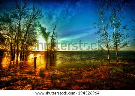 Beautiful HDR scene of a warm, golden sun rising above the shores of an idyllic, calm lake in the Canadian wilderness.