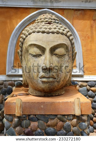 Beautiful head of Buddha in a beautiful garden - stock photo