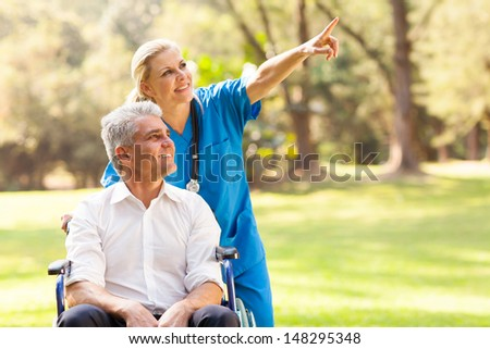 beautiful healthcare worker taking disabled patient for a walk outdoors - stock photo