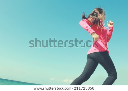 Beautiful healthy girl in pink running on the beach - stock photo