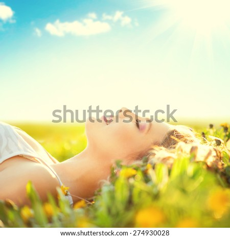 Beautiful Healthy Girl lying on summer field with flowers. Outdoors. Enjoy Nature. Healthy Smiling Girl on spring lawn. Allergy free concept. Freedom. Happy person outdoor - stock photo