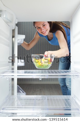 Beautiful healthy girl taking a salad from the refrigerator - stock photo