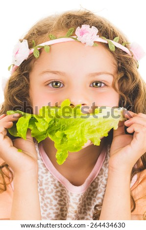 Beautiful healthy little curly girl enjoying eating a lettuce leaf  isolated on white - stock photo
