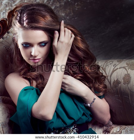 Beautiful  healthy luxurious hair, close-up. Young attractive woman in green dress sits on a beautiful sofa - stock photo