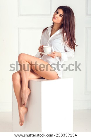 Beautiful healthy sexy brunette woman in white shirt with a cup of tea, posing sitting on a white cube space board on a bright interior background