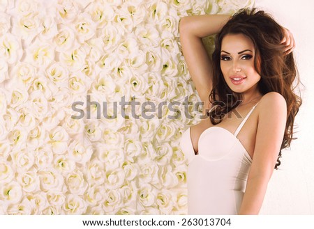 Beautiful healthy slim sexy brunette girl in white sporty underwear lingerie on bright roses wall background with copy space - stock photo