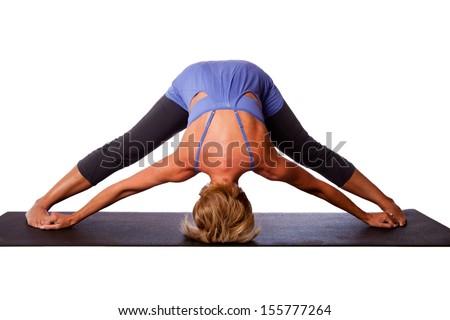 Beautiful healthy woman doing inversion Standing Intense Spread Leg Prasarita Padottanasana yoga pose with head on floor, on white. - stock photo